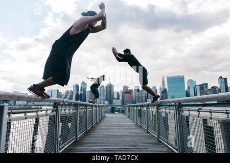 Los Estados Unidos, Nueva York, Brooklyn, tres hombres jóvenes haciendo Parkour salta en el embarcadero delante de Manhattan