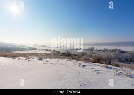 Paisaje invernal rural, los rayos del sol en una neblina de blue sky Acuéstese en un sinuoso río y campos cubiertos de nieve, arbustos y árboles.