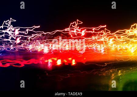 Diferentes senderos de luz de faroles multicolores y autos pasando la dispersión en la oscuridad, la larga exposición urbana de fondo abstracto