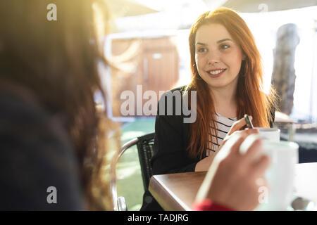 Retrato de mujer joven pelirroja con nariz penetrante mirando a su amiga en cafeterías