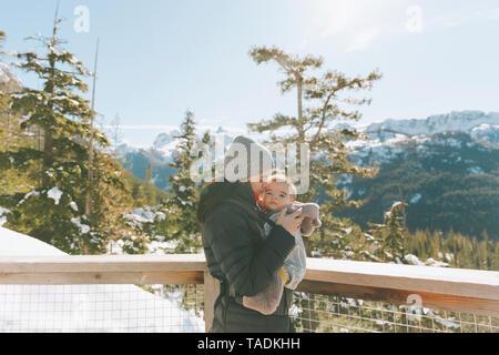 La madre sostiene a su hijo en una plataforma de observación, mirando hacia Squamish, Canadá