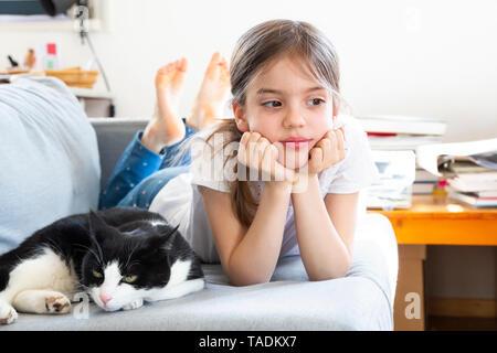 Retrato de niña acostada sobre el sofá con la cat.