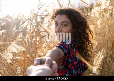Mujer joven de pie en el prado, sosteniendo la mano de un hombre joven