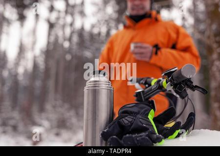 Hombre teniendo un descanso de mountainbike viaje en bosque de invierno con una bebida caliente