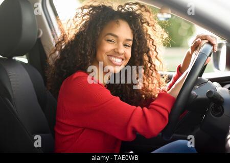 Retrato de mujer joven feliz en un coche Foto de stock
