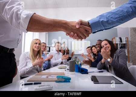 Dos profesionales masculinos un apretón de manos con el equipo por estar Aplaudiendo después de una exitosa reunión
