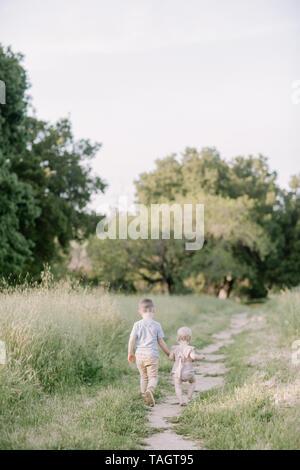 Gran Hermano y hermana de bebé abrazo en un campo