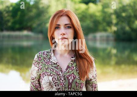 Frescos y seguros de joven mujer vistiendo patrón floral vestido con largo pelo rojo de pie junto al lago - auténtico pueblo real