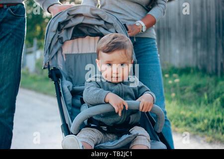 Cute Baby Boy 8-9 meses sentado en la silla de paseo con papá y mamá caminando por la carretera de pueblo afuera, sensibilidad al concepto de naturaleza