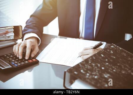 Contable o financiero manos inspector haciendo informe, calcular o controlar el equilibrio. Internal Revenue Service inspector financiero comprobación de hombre Foto de stock