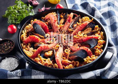 Español fideuá, Paella de fideos con marisco - langostinos, pescado blanco, carne, calamares, mejillones en un pan negro sobre una tabla concreta con los ingredientes, ho