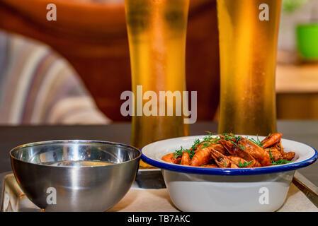 Camarones preparados con eneldo en un recipiente sobre la mesa con dos vasos de cerveza y agua
