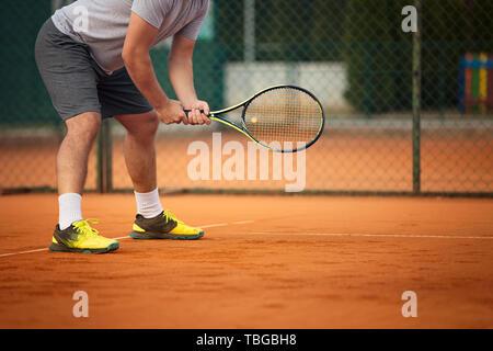 Cerca de hombre con raqueta de tenis en tierra batida. El Tribunal es el atardecer. Hombre sujetando raqueta de tenis