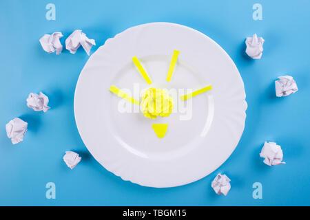Idea conceptos Bombilla con papel arrugado sobre fondo azul.