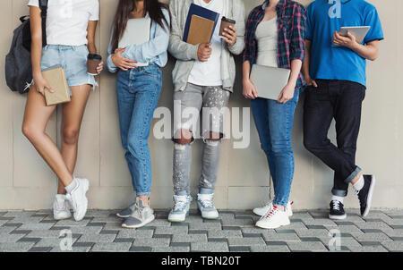 Los adolescentes en campus permanente de pared, dispositivos de sujeción y libros