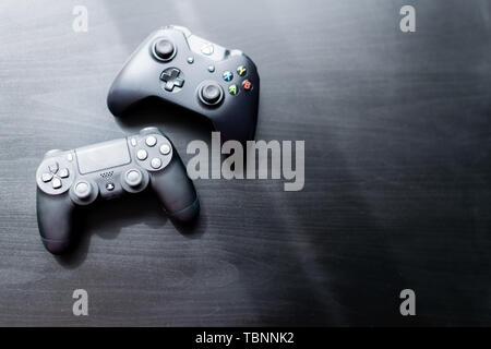 Controlador de Xbox y Playstation sat uno junto al otro en un fondo oscuro