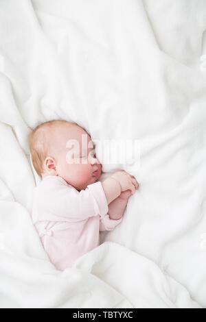 Bebe Durmiendo, 3 meses cabrito en tela rosa dormir sobre una sábana blanca, niño dormido en la cama