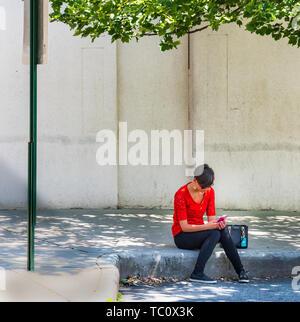 En Asheville, Carolina del Norte, EE.UU-5/31/19: un solitario joven en camisa roja se sitúa en la calle Acera mirando teléfono inteligente, enmarcadas por miembro del árbol y signo de la calle.