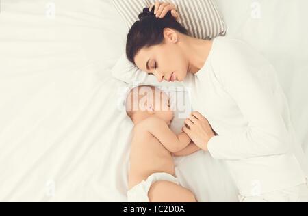 Joven madre y su lindo bebé durmiendo en la cama