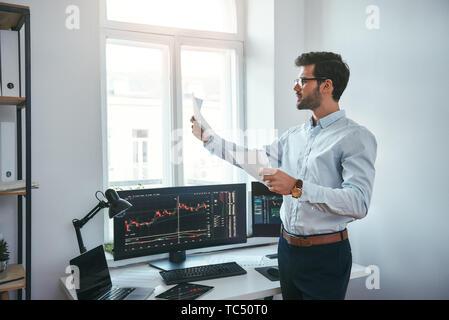 Estrategia de trading. Inteligente y joven comerciante en anteojos mirando informes financieros y analizar gráficos comerciales mientras está de pie delante de las pantallas de las computadoras en la oficina moderna. Corredor de bolsa. El mercado Forex. Concepto de comercio