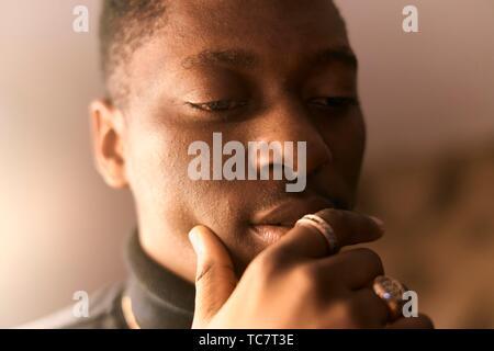 Joven reflexivo, mano a acariciar los labios, en Munich, Alemania.