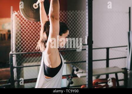 Athletic morena joven haciendo algunos ejercicios de levantamiento de pesas.