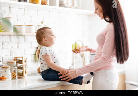 Encantadora madre ofreciendo fresco verde manzana a su lindo bebé