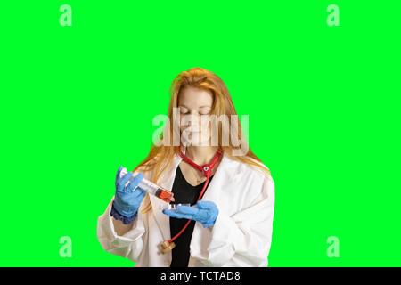 Jengibre jovencita rubia en Bata de laboratorio y guantes con estetoscopio sosteniendo petri de coloridos líquidos.