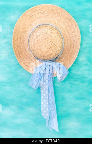 Solo sombrero de paja con cinta azul en un fondo de colores verde azulado