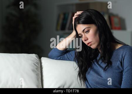 Mujer triste pensar mirando lejos sentados en un sofá en la noche en su domicilio.