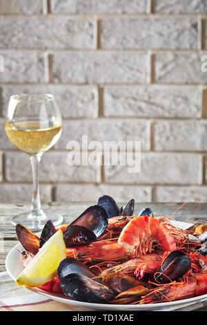 Close-up de una mezcla de mejillones, almejas y langostinos con un vaso de vino blanco y una pared de ladrillos en el fondo, vista desde arriba