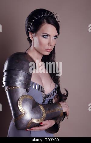 Mujer guerrera. Fantasy fashion idea. hermosa chica con armadura ortrait de Guerrero, a una dama hermosa morena vestida con un traje gris brillante, maquillaje.