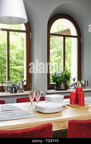 Sillas rojas en la mesa de comedor con ventanas en arco británico e irlandés de derechos sólo