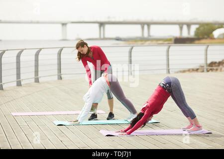 Longitud total retrato de mujeres contemporáneas hacer yoga en el exterior por el agua con la instructora de ayudarlas, espacio de copia