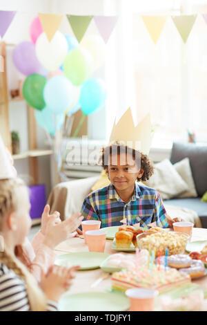 Retrato de afroamericanos sonriente niño usando crown sentado en la tabla mientras celebrando un cumpleaños con amigos Foto de stock