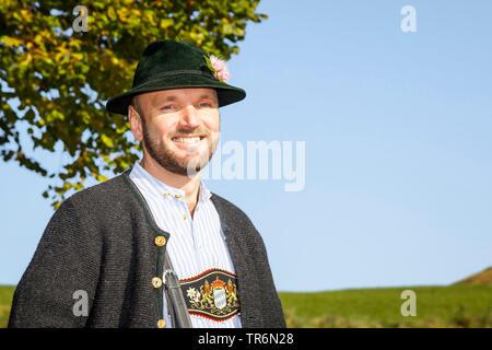 Vestido tradicional bávaro de hombre con sombrero Tirolés en un camino de campo, Alemania, Baviera