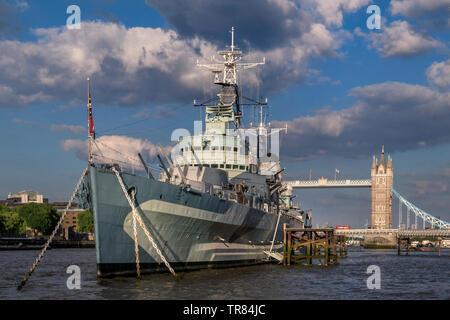 HMS Belfast atracción turística barco, amarrado en el Río Támesis en horas de la tarde la luz del sol, con el Tower Bridge y London Bus Rojo cruzar London SE1 Foto de stock
