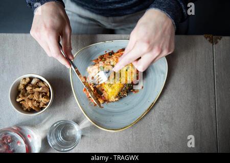 Comer en un restaurante, un hombre comiendo lasaña, hombre teniendo lunsh