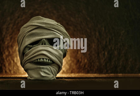 Momia cubiertas por la ropa en cráneo decorado en halloween cosplay y luz sobre fondo oscuro Foto de stock