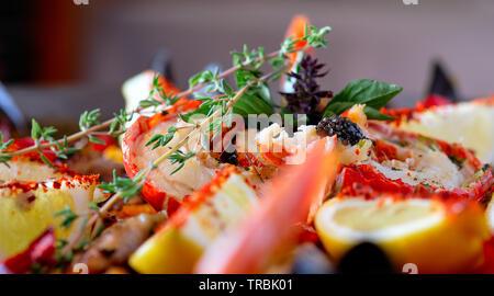 Cerrar imagen ingredientes maduros de preparado de paella sirve cocina tradicional española por país, colores brillantes. Plato aderezado con rodajas de limón, lob
