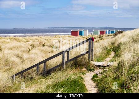 Camino a través de dunas y una escalera de madera que conduce a la playa con coloridas casetas de playa en la costa de Moray Firth. Findhorn, Moray, Escocia, Reino Unido, Gran Bretaña