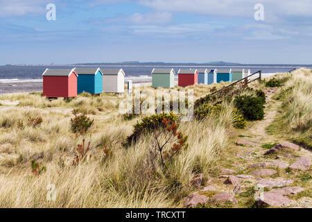 Ruta a través de las dunas de arena por encima de la playa de Findhorn con coloridas casetas de playa en la costa de Moray Firth. Findhorn, Moray, Escocia, Reino Unido, Gran Bretaña