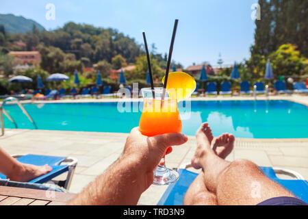 Joven disfrutando con piña cóctel en la piscina. Hombre sujetando beber alcohol y acostado en la hamaca. Relajarse en vacaciones