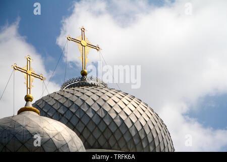 Cerca de las dos cúpulas de la iglesia con cruces doradas contra el cielo azul con nubes, enfoque suave, copyspace