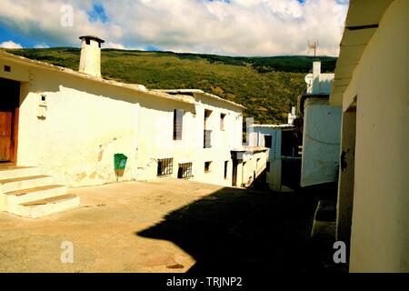 Calle con rústicas casas encaladas en la aldea de Sierra Nevada Capileira, Las Alpujarras, cerca de Granada, España.
