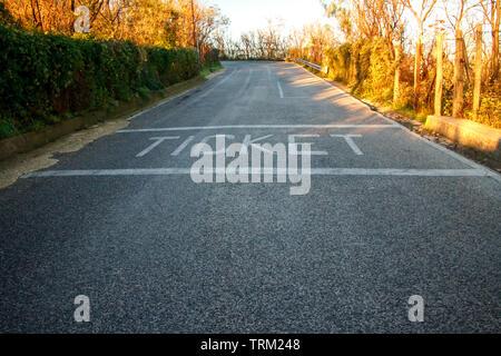 Antecedentes de la carretera con el boleto de inscripción al amanecer y los primeros rayos de sol, los árboles y el césped al lado de la carretera, el concepto de viaje y moviendo fo
