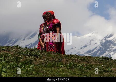 Ángulo de visión baja de dos vestidos tradicionalmente las mujeres locales posan para una fotografía contra un telón de fondo del Himalaya
