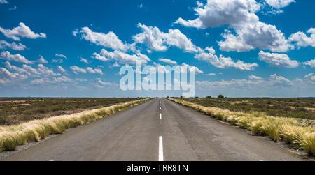 Imagen vibrante de la carretera del desierto y el azul cielo nublado