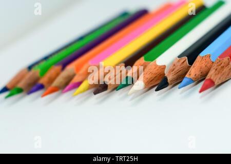 Close-up de una selección de varios lápices de color crayones, peguen dispuestos en una línea de fila gráfico de barras sobre fondo blanco, plano laical. Foc selectiva