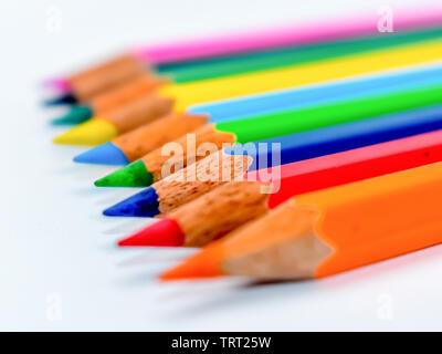Sobresalir entre la multitud concepto. Montón de variadas multi lápices de color crayones en rainbow arreglo sobre fondo blanco, plano laical. Geometría pa